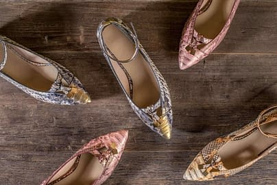 Women's leather shoes made from genuine python leather. Female high heel shoes lie on a wooden table