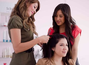 Two women teaching a crossdresser how to do hair and makeup